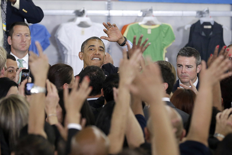 Photo - President Barack Obama waves after speaking at a Walmart store in Mountain View, Calif., Friday, May 9, 2014. Obama announced new steps by companies, local governments and his own administration to deploy solar technology, showcasing steps to combat climate change that don't require consent from a disinclined Congress. (AP Photo/Jeff Chiu)