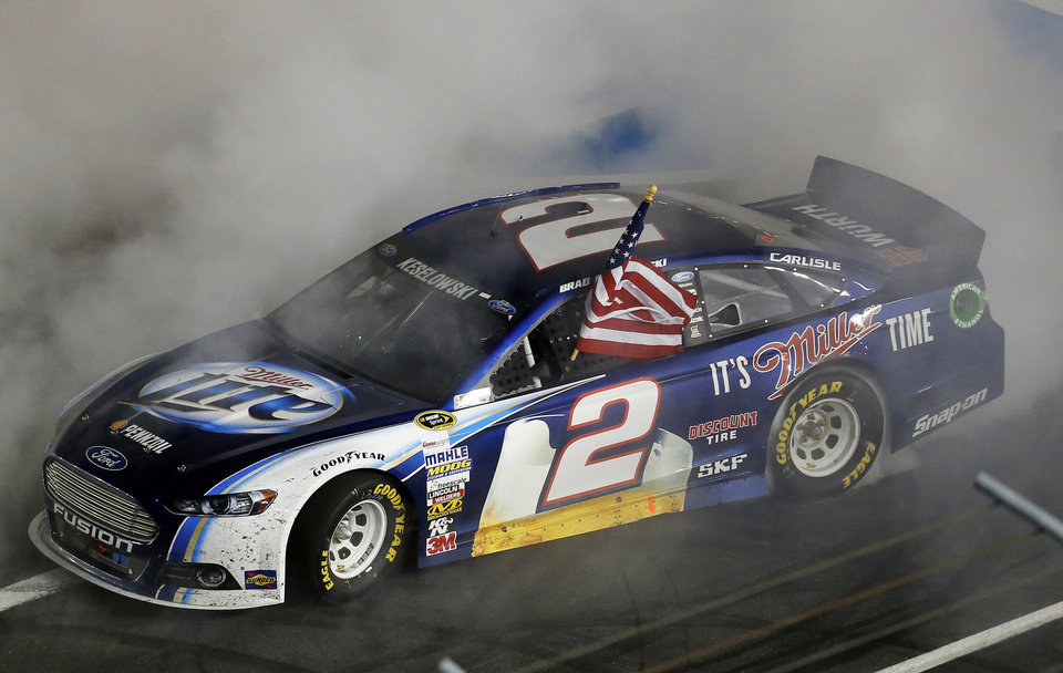 Photo - Brad Keselowski celebrates with a burnout after winning the NASCAR Sprint Cup Series auto race at Charlotte Motor Speedway in Concord, N.C., Saturday, Oct. 12, 2013. (AP Photo/Chris Keane)