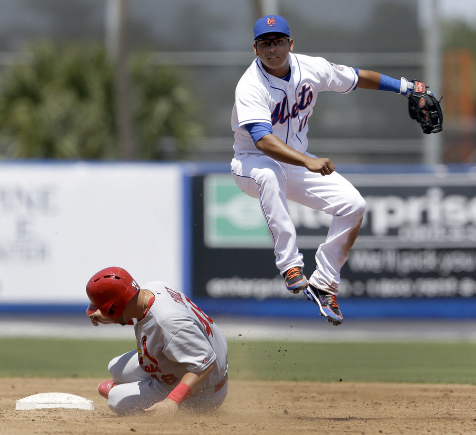 Photo - St. Louis Cardinals' Tony Cruz, left, is out at second as New York Mets shortstop Ruben Tejada turns the double play during the fourth inning of an exhibition spring training baseball game, Friday, March 29, 2013, in Port St. Lucie, Fla. The Cardinals' Daniel Descalso was out at first. (AP Photo/Jeff Roberson)