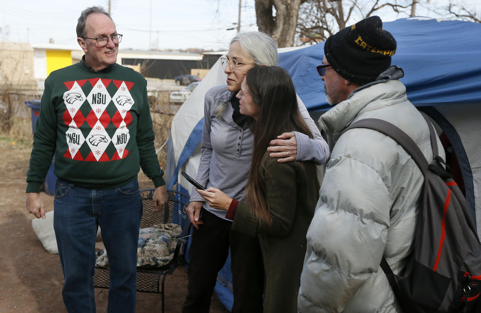 Photo - Founder and pastor of Joe's Addiction Jamie Zumwalt, 51, second from right, and volunteer Terry Fife, 66, hug as Fife's husband, Ben Hardcastle, 65, left, and Luther, 52, who preferred not to give his last name, look on while people eat lunch out of a tent at 6100 S Cox, near the original location of Joe's Addiction, in Valley Brook, Okla., Monday, Dec. 23, 2019. While the new site for Joe's Addiction is not ready, Zumwalt and others continue to help the community of people in need who were being served by Joe's Addiction. [Nate Billings/The Oklahoman]