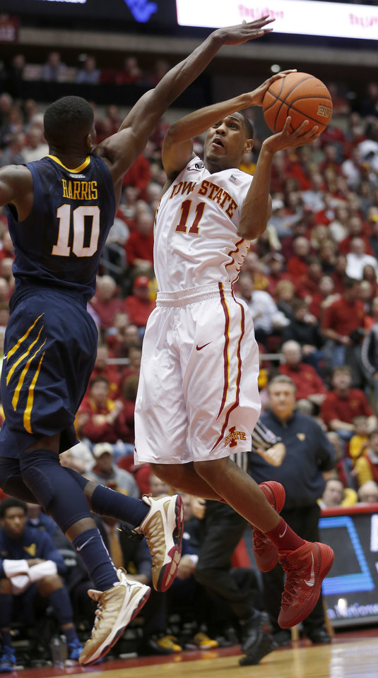 Photo - Iowa State guard Monte Morris goes up for a shot over West Virginia guard Eron Harris during the first half of an NCAA college basketball game in Ames, Iowa, Wednesday, Feb. 26, 2014. (AP Photo/Justin Hayworth)