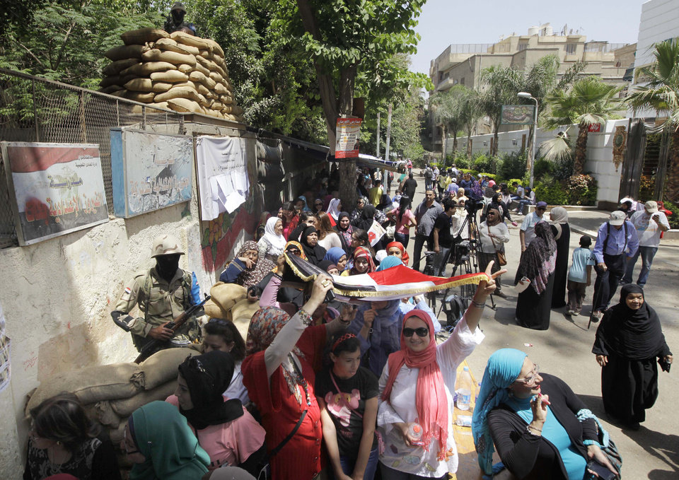 Photo - Voters line up as some take shade under a national flag outside a polling station to vote for president in an election that comes nearly a year after the military's ouster of the nation's first freely elected president, the Islamist Mohammed Morsi in Cairo, Egypt, Monday, May 26, 2014. The man who removed Morsi, retired military chief Field Marshal Abdel-Fattah el-Sissi, is practically assured of a victory in the vote.(AP Photo/Amr Nabil)