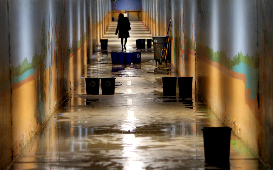 A visitor at the State Capitol walks through a maze of trash cans and water puddles in the pedestrian tunnel in Oklahoma City, Monday February 25, 2013. Photo By Steve Gooch, The Oklahoman