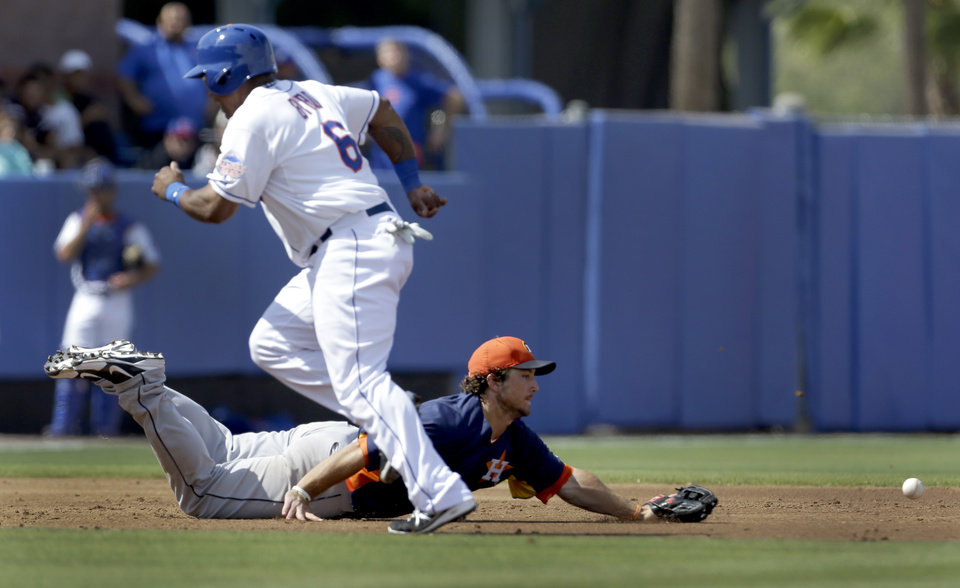 Photo - Houston Astros third baseman Brett Wallace dives but cannot reach a ball hit for an RBI single by New York Mets' Ike Davis as the Mets' Marlon Byrd (6) rounds third and heads in to score during the third inning of an exhibition spring training baseball game Saturday, March 9, 2013, in Port St. Lucie, Fla. (AP Photo/Jeff Roberson)