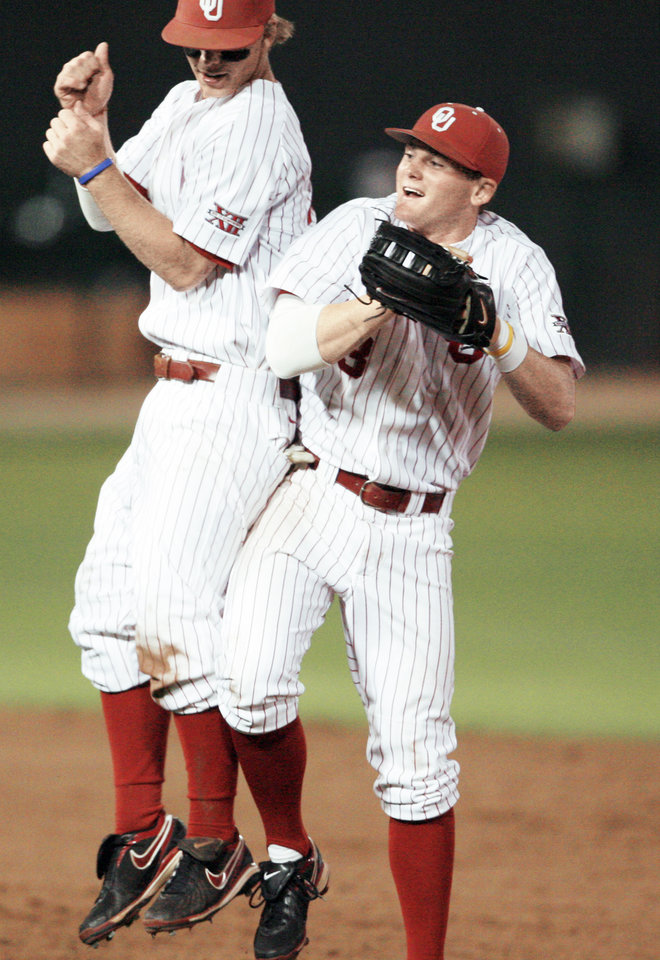 Photo - Garrett Buechele, left, and Casey Johnson celebrate after Oklahoma's win over Wichita State in their NCAA Regional opener Friday at Mitchell Park in Norman.  Photo by Steve Sisney, The Oklahoman