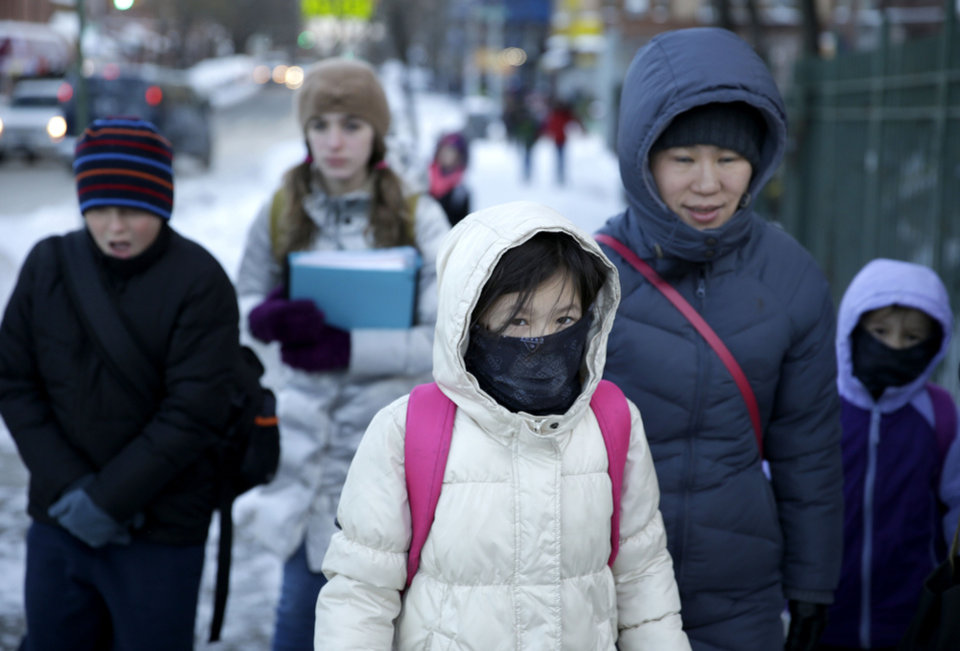 Photo - Parents and children arrive to school bundled up against the cold in the Brooklyn borough of New York, Wednesday, Jan. 22, 2014.  A winter storm stretched from Kentucky to New England and hit hardest along the heavily populated Interstate 95 corridor between Philadelphia and Boston. Snow began falling at midmorning Tuesday in Philadelphia and dumped as much as 14 inches by Wednesday morning, with New York seeing almost as much.  Boston and Philadelphia officials ordered schools closed Wednesday, but in New York City, the nation's largest public school system remained open.  (AP Photo/Seth Wenig)