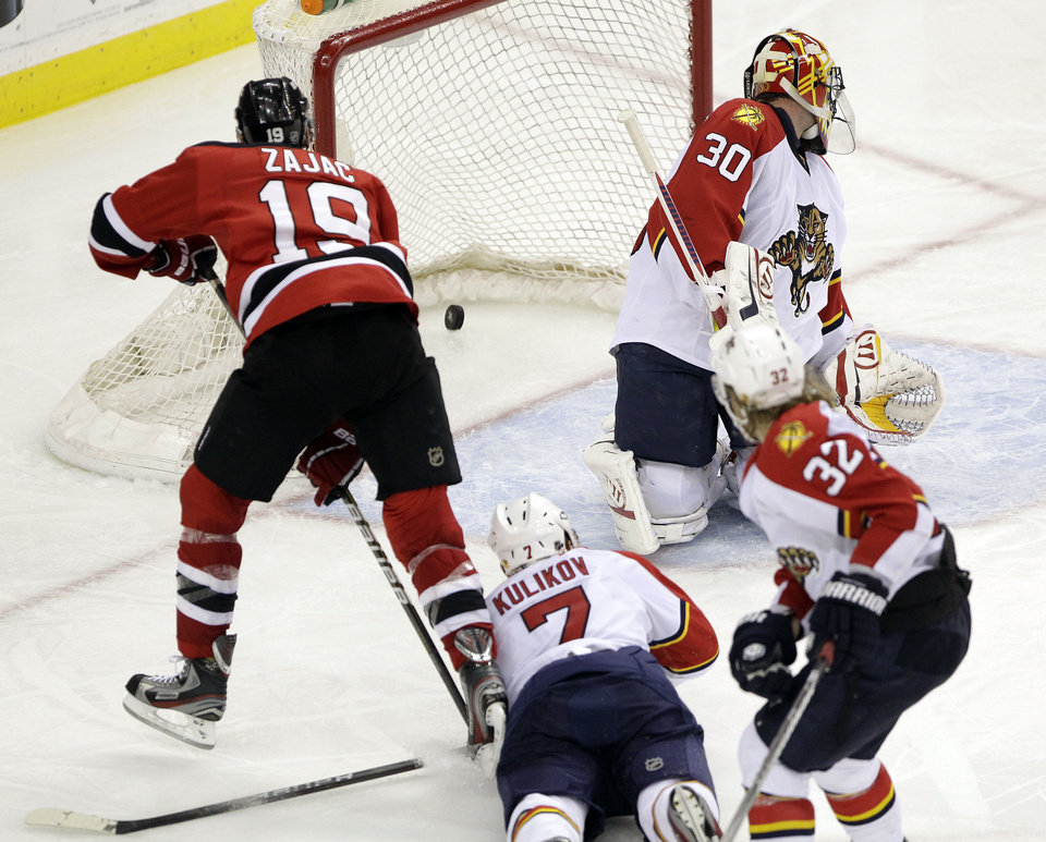 Photo -   New Jersey Devils' Travis Zajac (19) scores the game-winning goal on Florida Panthers goalie Scott Clemmensen (30) as Dmitry Kulikov (7), of Russia, and Kris Versteeg (32) defend during the overtime of Game 6 of a first-round NHL hockey Stanley Cup playoff series, Tuesday, April 24, 2012, in Newark, N.J. The Devils won 3-2, forcing Game 7. (AP Photo/Julio Cortez)