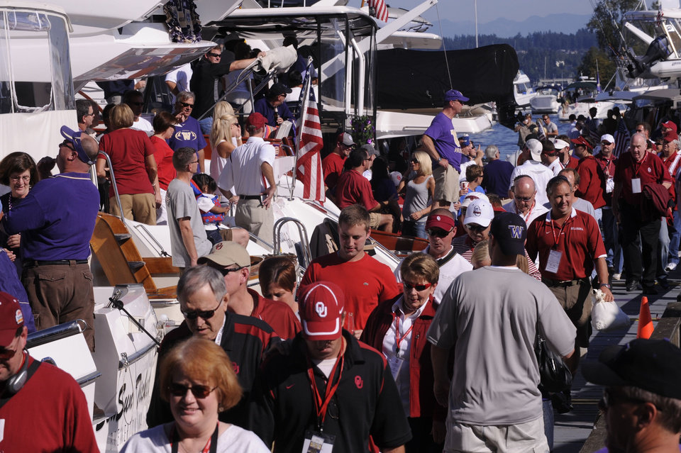 Photo - NCAA COLLEGE FOOTBALL - UNIVERSITY OF WASHINGTON VS. UNIVERSITY OF OKLAHOMA (OU) - 091308 - There was plenty of Oklahoma red mixed in with the Washington purple along the shores of Lake Washington as fans arrived via boats for the game.  ORG XMIT: 0406486000