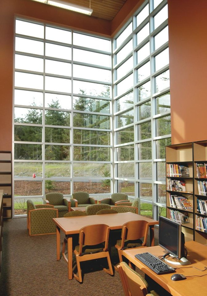 Photo - Flintco Inc. built the Lummi Nation School in Belllingham, Wash., to reflect the Lummi long house tradition while respecting the historic Lummi attachment to the ocean and nature in general. Here, tall walls of windows allow natural light to flow into a reading area of the school.	ORG XMIT: 0802222248528688