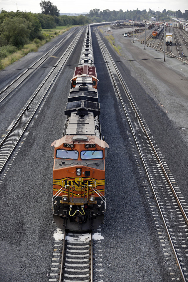 Photo - An oil train sits idled on tracks, blocked from progress by protesters blocking the track ahead Tuesday, Sept. 2, 2014, in Everett, Wash. About a dozen demonstrators blocked the tracks at a Burlington Northern Santa Fe yard to protest oil and coal export terminals in the Northwest. (AP Photo/Elaine Thompson)