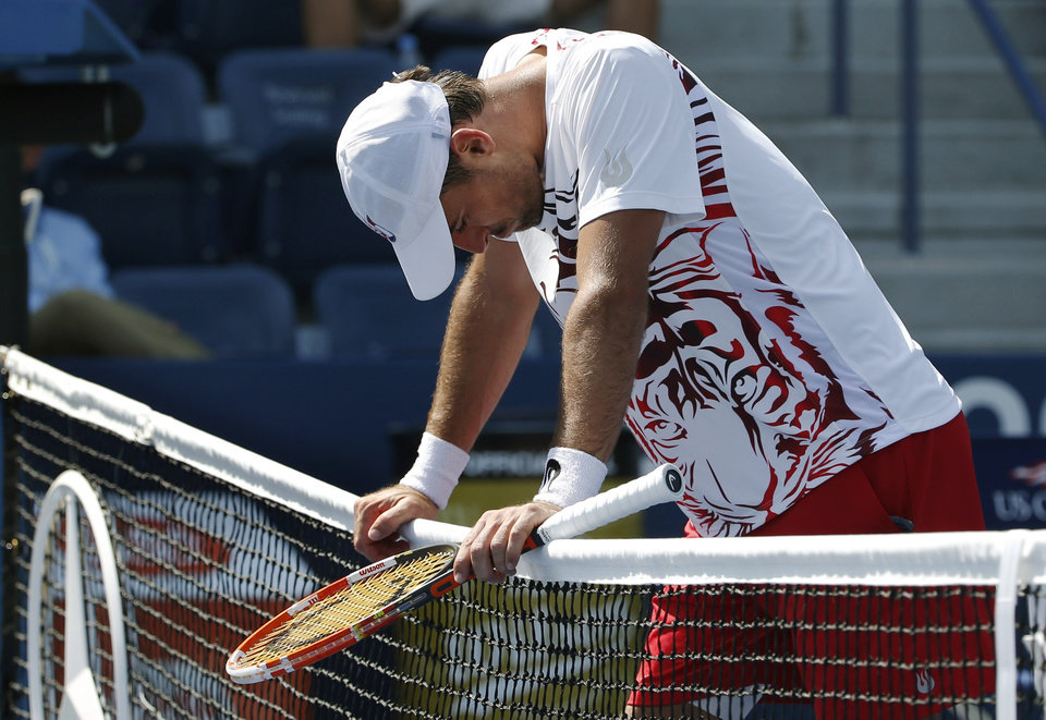 Photo - Ivan Dodig, of Croatia, leans on the net as he forfeits the match to Feliciano Lopez, of Spain, because of injury in the fifth set during the second round of the 2014 U.S. Open tennis tournament, Wednesday, Aug. 27, 2014, in New York. (AP Photo/Kathy Willens)