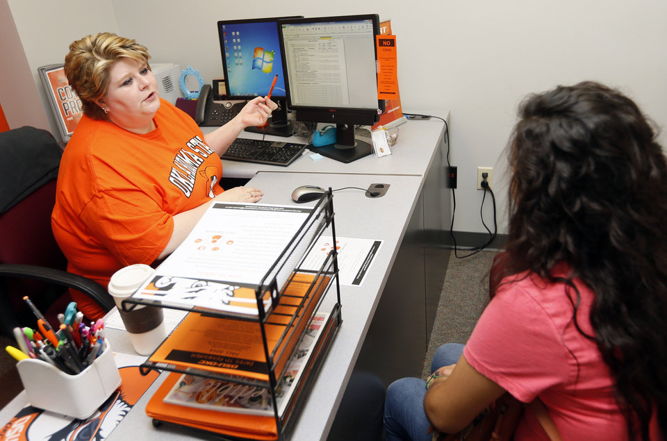 Photo -  Sarah Stringfield, liberal arts divisional adviser, helps freshman Diana Trejo, 18, during the Orange Ticket enrollment event July 13 at Oklahoma State University-Oklahoma City. [Photo by Nate Billings, The Oklahoman]
