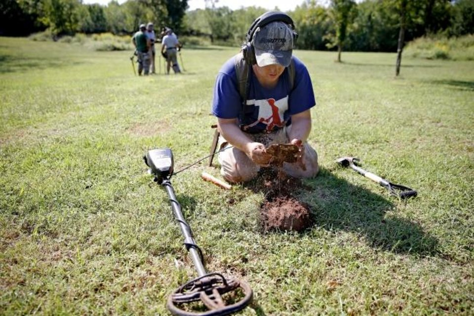 Photo -  Justin Finley, of Oklahoma City, unearths an old oil can. [Bryan Terry/The Oklahoman]