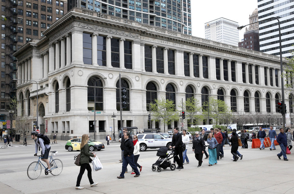"""Photo - In this Wednesday, May 14, 2014 photo, pedestrians  walk past the Cultural Center along Michigan Ave. in Chicago. In 2012, Mayor Rahm Emanuel promised to transform Chicago from the foundation up with mega projects bankrolled entirely by private investors in exchange for a chunk of the profits. The Chicago Infrastructure Trust was born as a """"breakout strategy"""" for modernizing buildings, bridges and broadband without waiting for Washington handouts. The city's first deal, known as Retrofit Chicago, with Bank of America, includes landmarks like City Hall, the Harold Washington Library, and the Cultural Center, and is expected to generate annual utility bill savings of $1.5 million. (AP Photo/Charles Rex Arbogast)"""