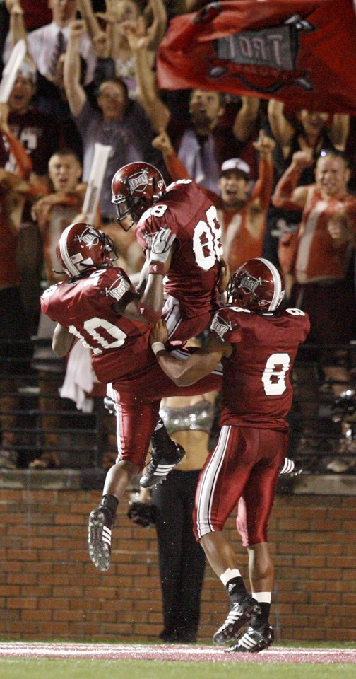 Photo - Troy players Gerald Tate (10), Kennard Burton (88) and Gary Banks celebrate after their team's first touchdown in the first quarter during the college football game between the Troy University Trojans and the Oklahoma State University Cowboys at Movie Gallery Veterans Stadium in Troy, Ala., Friday, September 14, 2007. BY MATT STRASEN, THE OKLAHOMAN
