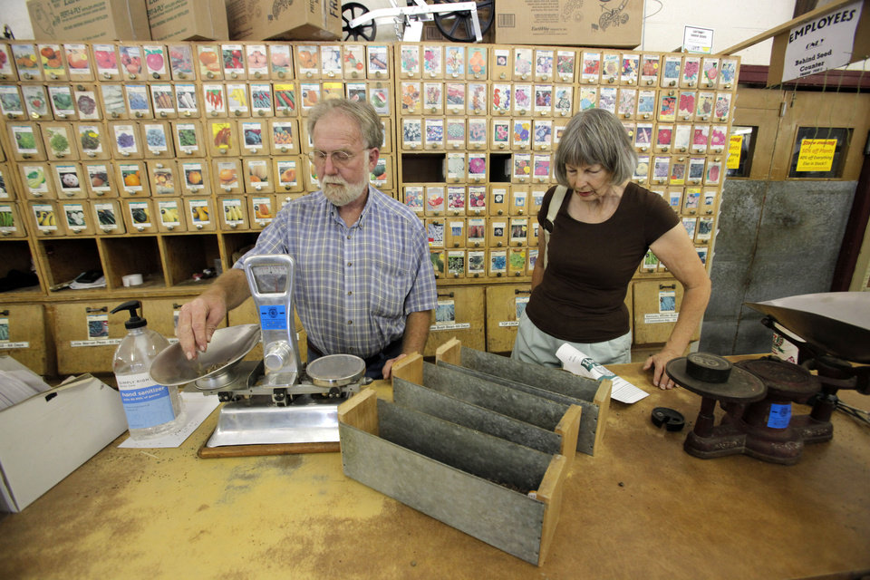 Photo - Horn Seed Co. employee Rick Thomas helps JoAnne Vervinck look for flower seeds. Thomas has worked at Horn's for 34 years and the business is closing after 91 years.  Steve Gooch - The Oklahoman