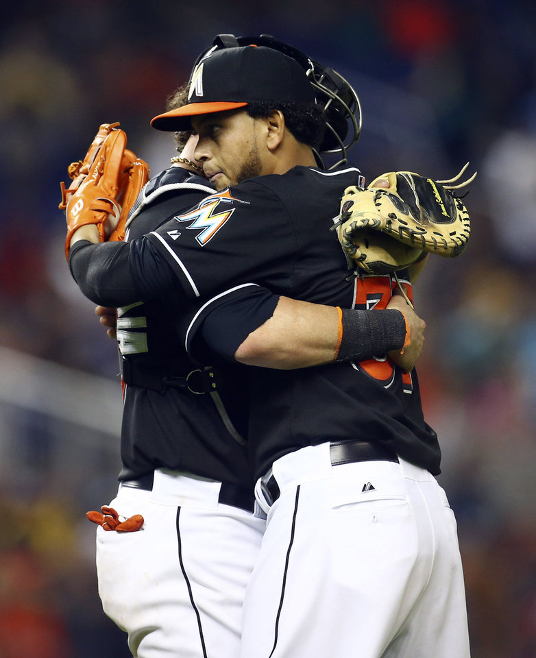 Photo - Miami Marlins starting pitcher Henderson Alvarez, right, hugs catcher Jarrod Saltalmacchia after a baseball game against the Seattle Mariners in Miami, Saturday, April 19, 2014.  The Marlins won 7-0. (AP Photo/J Pat Carter)