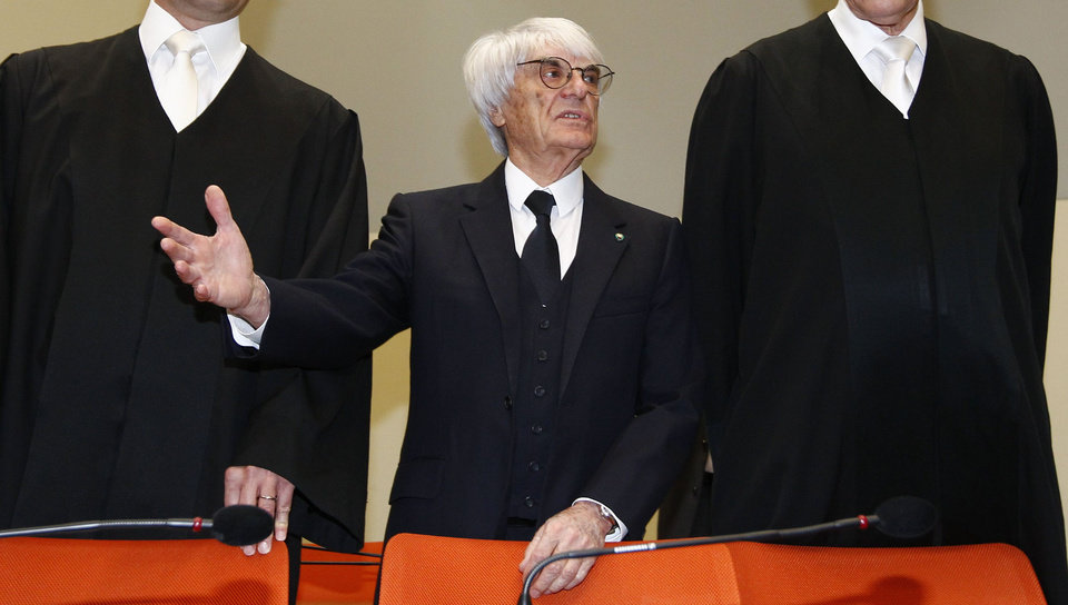 Photo - F1 CEO Bernie Ecclestone, center, stands with his lawyers as he arrives in the  court in Munich, southern Germany, Thursday, April 24, 2014. Ecclestone is charged with bribery and incitement to breach of trust