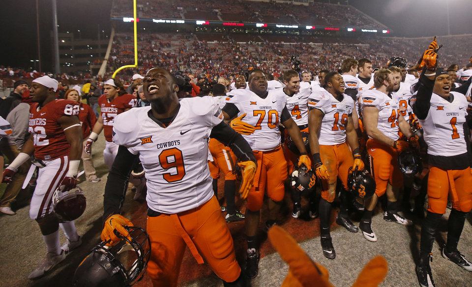 Photo - Oklahoma State, including Gyasi Akem (9), celebrate after winning a Bedlam college football game between the University of Oklahoma Sooners (OU) and the Oklahoma State Cowboys (OSU) at Gaylord Family-Oklahoma Memorial Stadium in Norman, Okla., Saturday, Dec. 6, 2014. Photo by Bryan Terry, The Oklahoman