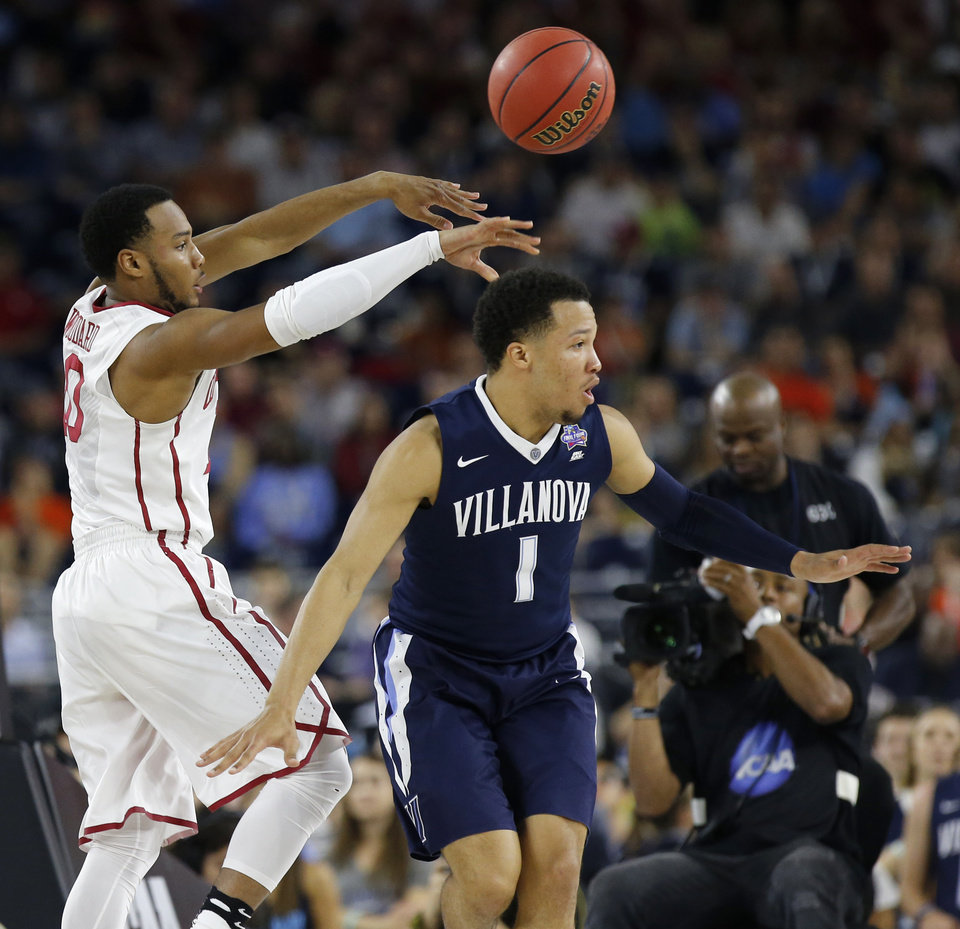 Photo - Oklahoma's Jordan Woodard (10) passes over Villanova's Jalen Brunson (1) during the national semifinal between the Oklahoma Sooners (OU) and the Villanova Wildcats in the Final Four of the NCAA Men's Basketball Championship at NRG Stadium in Houston, Saturday, April 2, 2016. Photo by Nate Billings, The Oklahoman