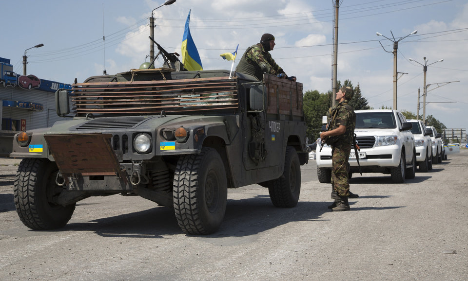 Photo - Ukrainian government army's soldiers stand guard next to the cars of Convoy of the OSCE mission in Ukraine at a check-point in the village of Debaltseve, Donetsk region, eastern Ukraine Thursday, July 31, 2014. Members of the OSCE mission in Ukraine are attempting to reach a place of Malaysia Airlines plane crash. (AP Photo/Dmitry Lovetsky)