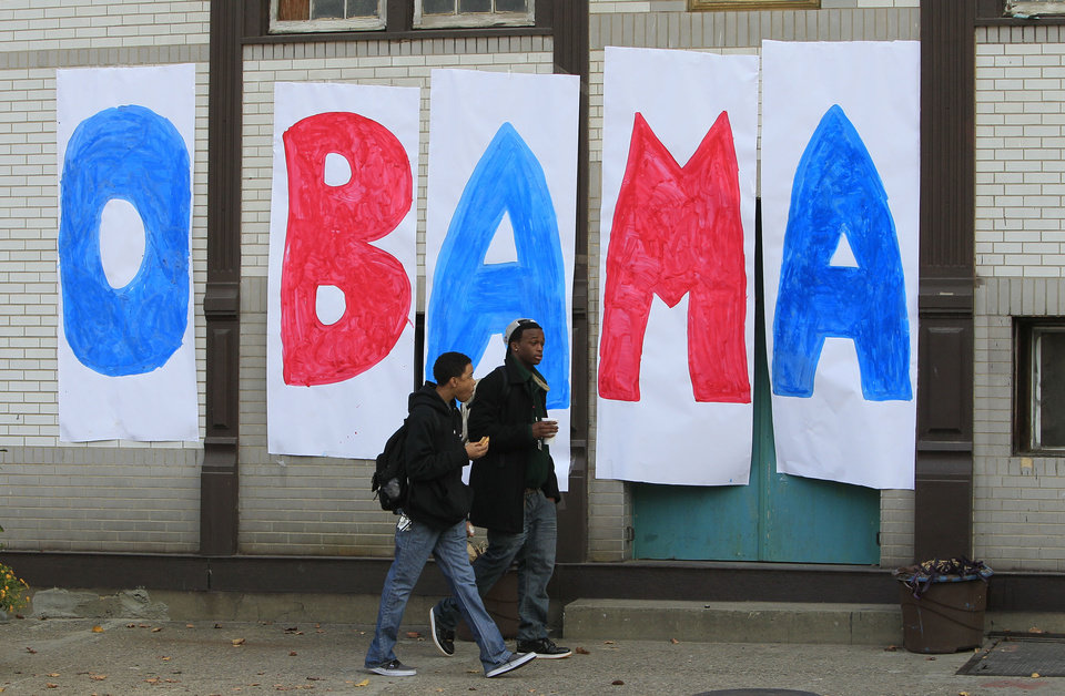 Photo -   Jaylen Williams, left, and Sean Tyus walk past a home made Obama sign on their way to school, Wednesday, Nov. 7, 2012, in the Over-the-Rhine neighborhood of downtown Cincinnati. President Barack Obama captured a second White House term on Tuesday over the challenge by Republican Mitt Romney. (AP Photo/Al Behrman)