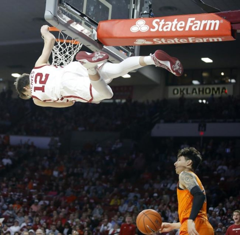 Photo -  OU's Austin Reaves (12) hangs on the rim over OSU's Lindy Waters III (21) after a dunk during the Sooners' 82-69 win Saturday in Norman. [Bryan Terry/The Oklahoman]