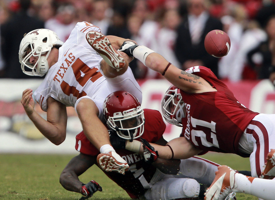 Photo -   Texas quarterback David Ash (14) fumbles after he was sacked by Oklahoma linebacker Tom Wort (21) and defensive back Tony Jefferson (1) during the second half of an NCAA college football game at the Cotton Bowl Saturday, Oct. 13, 2012, in Dallas. Oklahoma won 63-21. (AP Photo/Michael Mulvey)