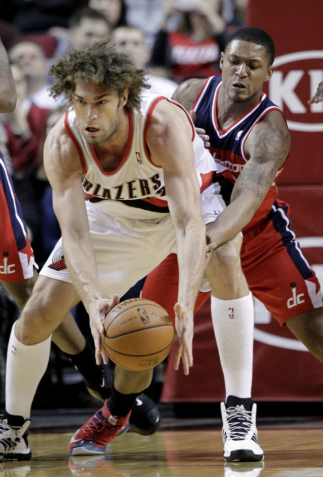 Photo - Washington Wizards guard Bradley Beal, right, reaches in on Portland Trail Blazers center Robin Lopez during the first half of an NBA basketball game in Portland, Ore., Thursday, March 20, 2014. (AP Photo/Don Ryan)