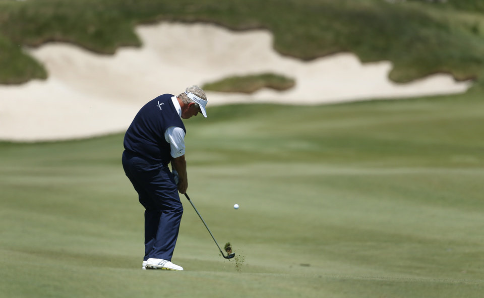 Photo - Colin Montgomerie hits a fairway shot on the fifth hole during the final round of the Senior PGA Championship golf tournament at Harbor Shores Golf Club in Benton Harbor, Mich., Sunday, May 25, 2014. (AP Photo/Paul Sancya)