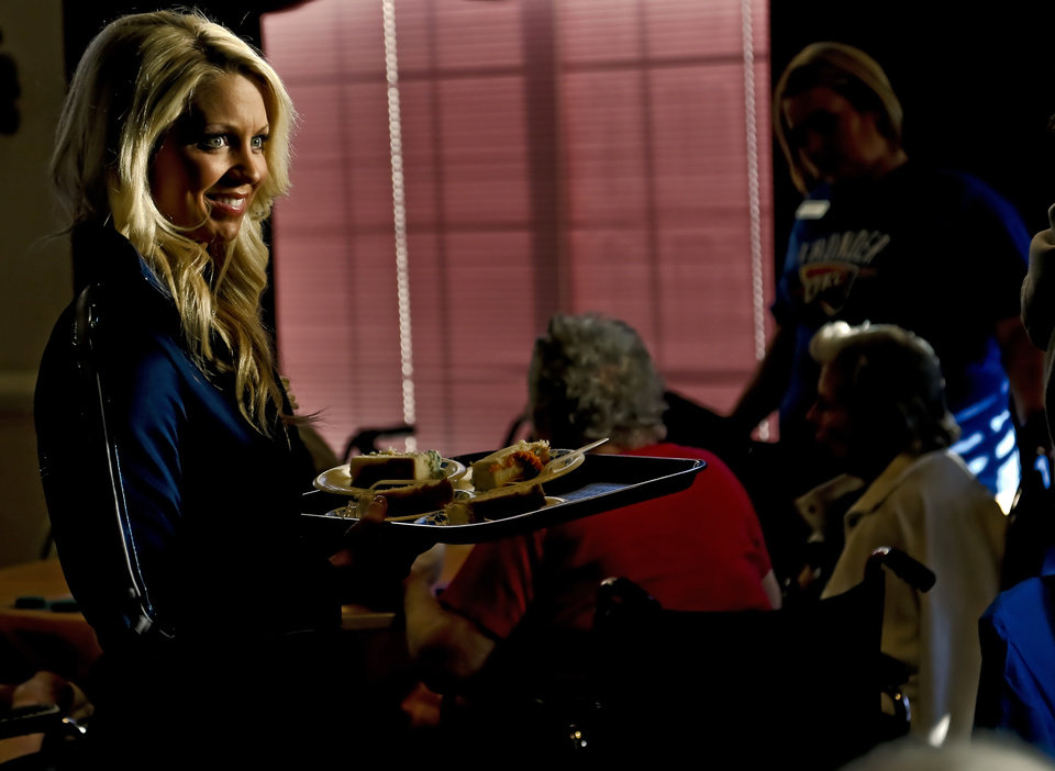 A member of the Thunder Girls serves cake to residents during the Oklahoma City Thunder's 1000th community appearance at Ranchwood Nursing Home on Tuesday, Nov. 27, 2012, in Yukon, Okla.   Photo by Chris Landsberger, The Oklahoman
