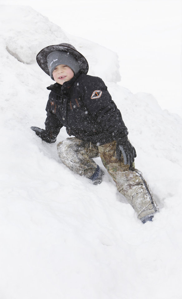 Photo - While Jeff Patton worked to clear the snow from in front of Classics Salon and Barber Shop in Edmond, his son, Chayton, 6, played in the snow.