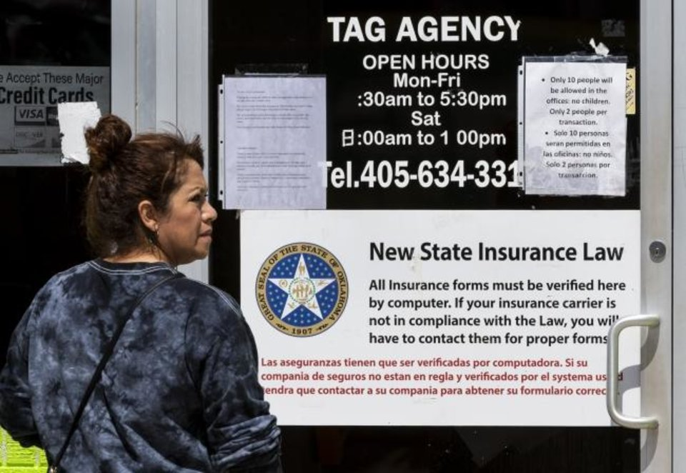 Photo -  A customer stands outside the 29th St. Tag Agency as she waits in line for service in Oklahoma City, Okla. on Tuesday, March 31, 2020. The tag agency only allows 10 people inside the location at one time.  [Chris Landsberger/The Oklahoman]