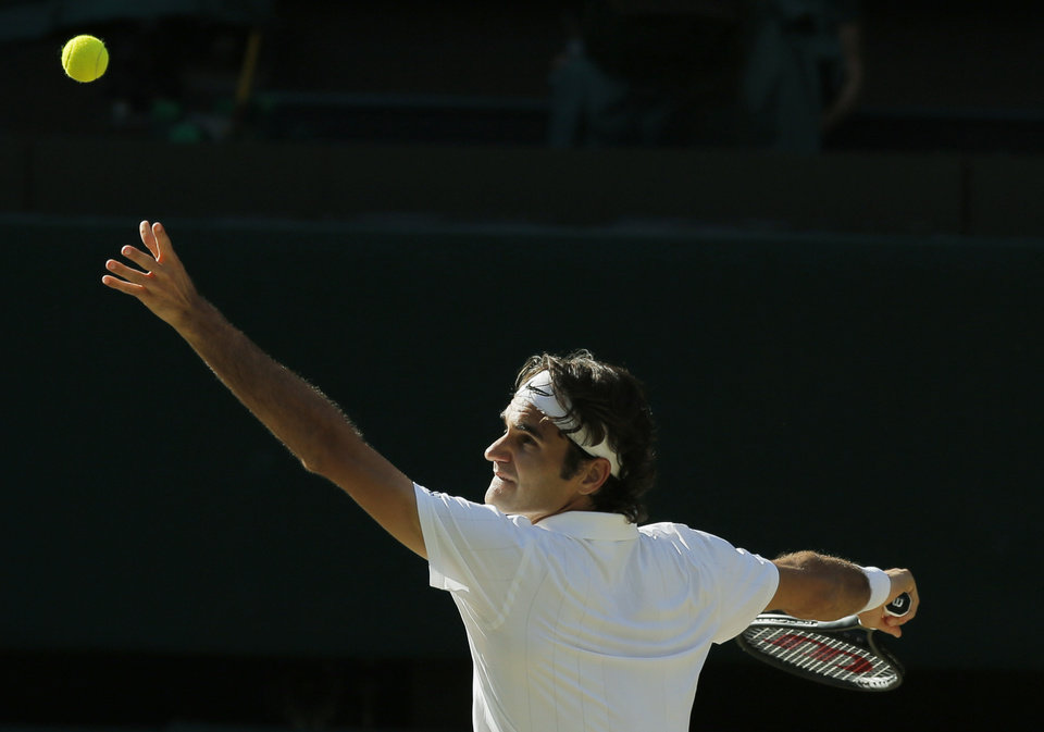 Photo - Roger Federer of Switzerland serves to Novak Djokovic of Serbia during their men's singles final match at the All England Lawn Tennis Championships in Wimbledon, London, Sunday, July 6, 2014. (AP Photo/Pavel Golovkin)