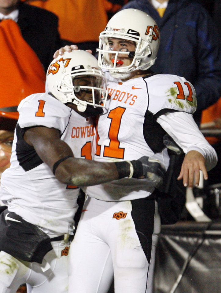 Photo - OSU's Zac Robinson (11) and Dez Bryant (1) celebrate a touchdown run by Robinson in the third quarter during the college football game between Oklahoma State University and University of Colorado at Folsom Field in Boulder, Colo., Saturday, Nov. 15, 2008. OSU won, 30-17. BY NATE BILLINGS, THE OKLAHOMAN