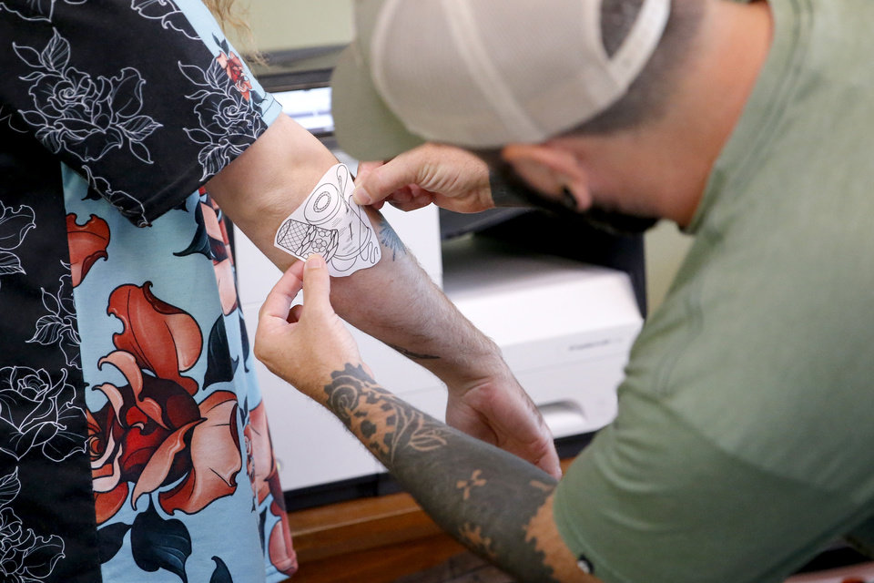 Photo - Wes Brooks, known as Lazlow, places a guide for a tattoo on the arm of Tyler Williams inside Altered Images in Oklahoma City, Wednesday, June 26, 2019. [Bryan Terry/The Oklahoman]