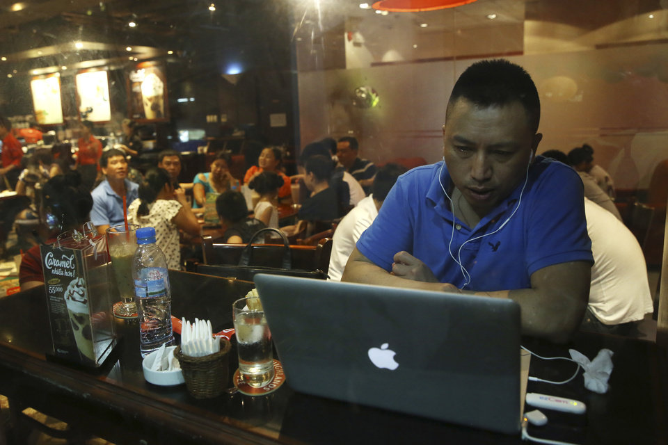 Photo - FILE - In this May 14, 2013 file photo, a Vietnamese man uses a 3G device to get online at a cafe in Hanoi, Vietnam. Vietnamese pro-democracy activists and bloggers are battling a gathering campaign of blocking, hacking and spying by a shadowy pro-government army of cyber warriors. Although they can't prove it, activists and analysts strongly suspect the Vietnamese state is involved in the campaign, which is hampering the country's democracy movement. (AP Photo/Na Son Nguyen, File)