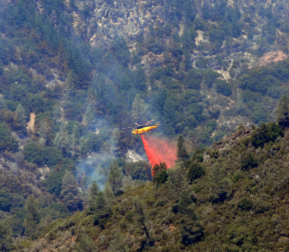 A helicopter drops fire retardant on the Ponderosa Fire deep in Battle Creek Canyon on Thursday, Aug. 23, 2012 west of Mineral, Calif.  The Ponderosa Fire is 57 percent contained, with full containment expected early next week. AP photo