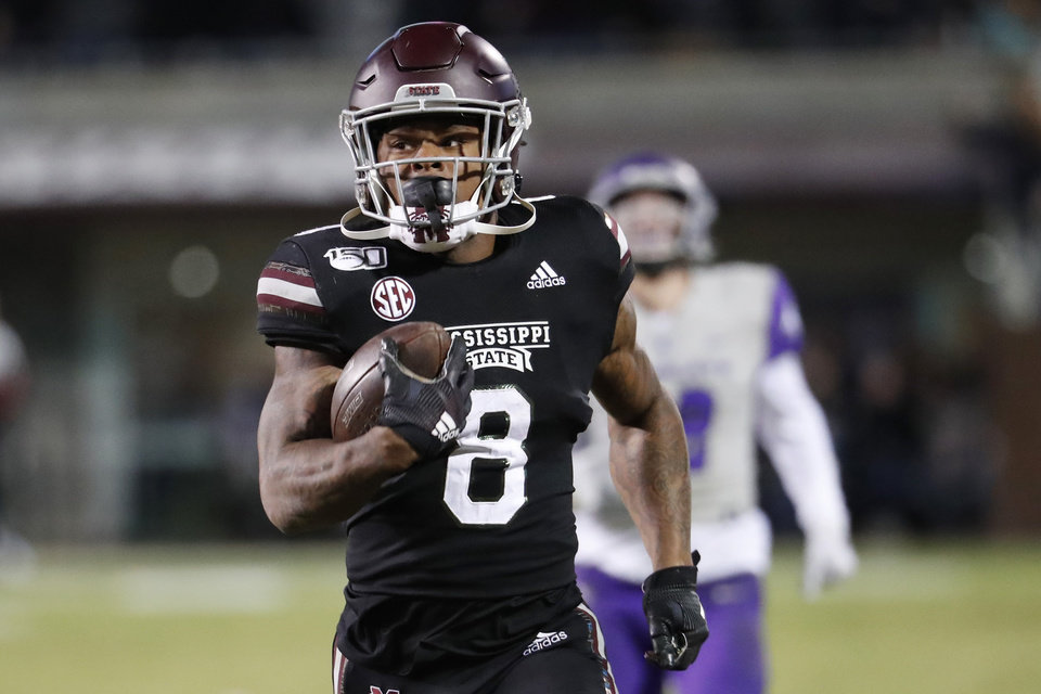 Photo - Mississippi State running back Kylin Hill (8) runs past Abilene Christian players on his way to an 88-yard touchdown pass reception during the first half of an NCAA college football game, Saturday, Nov. 23, 2019, in Starkville, Miss. (AP Photo/Rogelio V. Solis)