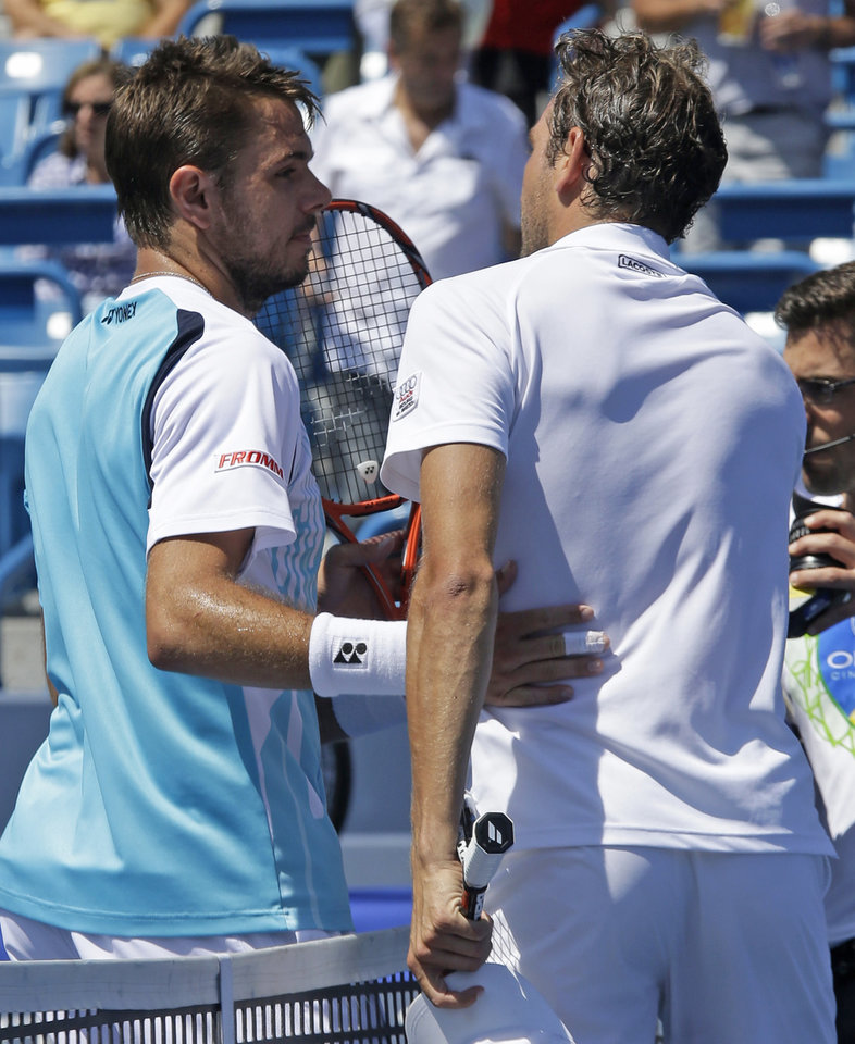 Photo - Stan Wawrinka, from Switzerland, left, congratulates Julien Benneteau, from France, after Benneteau upset Wawrinka 1-6, 6-1, 6-2, during a match at the Western & Southern Open tennis tournament, Friday, Aug. 15, 2014, in Mason, Ohio. (AP Photo/Al Behrman)