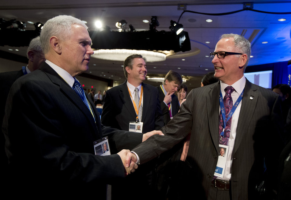Indiana Gov. Mike Pence, left, shakes hands with Walgreens CEO and President Gregory Wasson, right, during a break at the opening session of the National Governors Association 2013 Winter Meeting in Washington, Saturday, Feb. 23, 2013.   (AP Photo/Manuel Balce Ceneta)