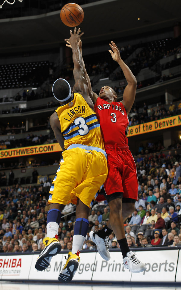 Denver Nuggets guard Ty Lawson, left, blocks a shot by Toronto Raptors guard Kyle Lowry during the first quarter of an NBA basketball game in Denver on Monday, Dec. 3, 2012. (AP Photo/David Zalubowski)