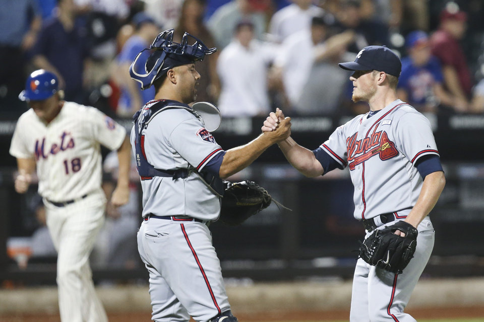 Photo - Atlanta Braves relief pitcher Craig Kimbrel, right, and catcher Gerald Laird, center, celebrate after the ninth inning of a baseball game against the New York Mets, Wednesday, Aug. 27, 2014, in New York. The Braves won 3-2. (AP Photo/John Minchillo)