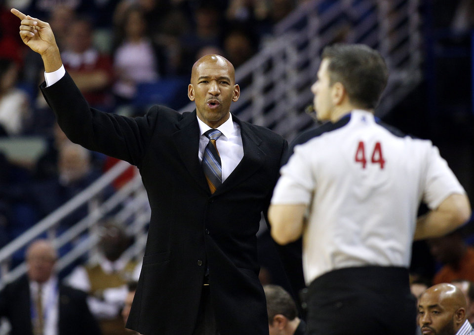 Photo - New Orleans Pelicans head coach Monty Williams, left, reacts during the first half of the NBA basketball game against the Golden State Warriors in New Orleans, Saturday, Jan. 18, 2014. (AP Photo/Jonathan Bachman)