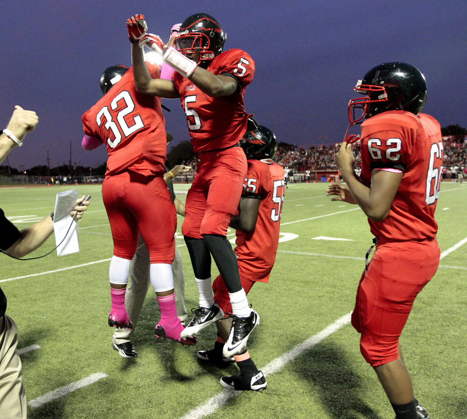 Del City's Davion Freeman (5) is congratulated after taking a free kick in for a touchdown following a safety by Midwest City in the first half in high school football on Friday, Sept. 20, 2013 in Del City, Okla.  Photo by Steve Sisney, The Oklahoman