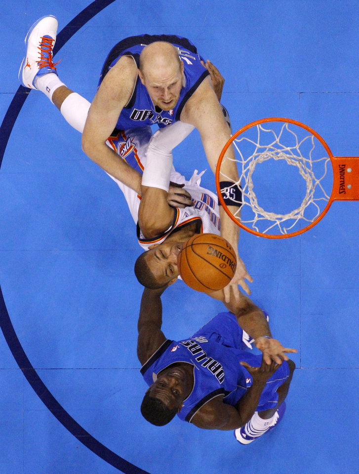 Photo - Oklahoma City's Russell Westbrook (0) goes to the basket between Dallas' Chris Kaman (35) and Darren Collison (4) during an NBA basketball game between the Oklahoma City Thunder and the Dallas Mavericks at Chesapeake Energy Arena in Oklahoma City, Thursday, Dec. 27, 2012.  Oklahoma City won 111-105. Photo by Bryan Terry, The Oklahoman