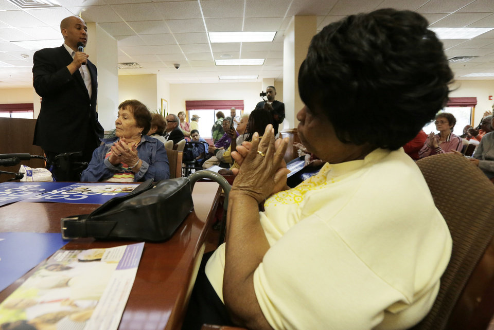 Photo - Newark Mayor Cory Booker, left, talks to supporters at a senior center, Tuesday, Oct. 15, 2013, in Newark, N.J. Booker will be going up against his Republican opponent Steve Lonegan Wednesday, Oct. 16, during a special election to fill New Jersey's vacant seat in the U.S. Senate. (AP Photo/Julio Cortez)