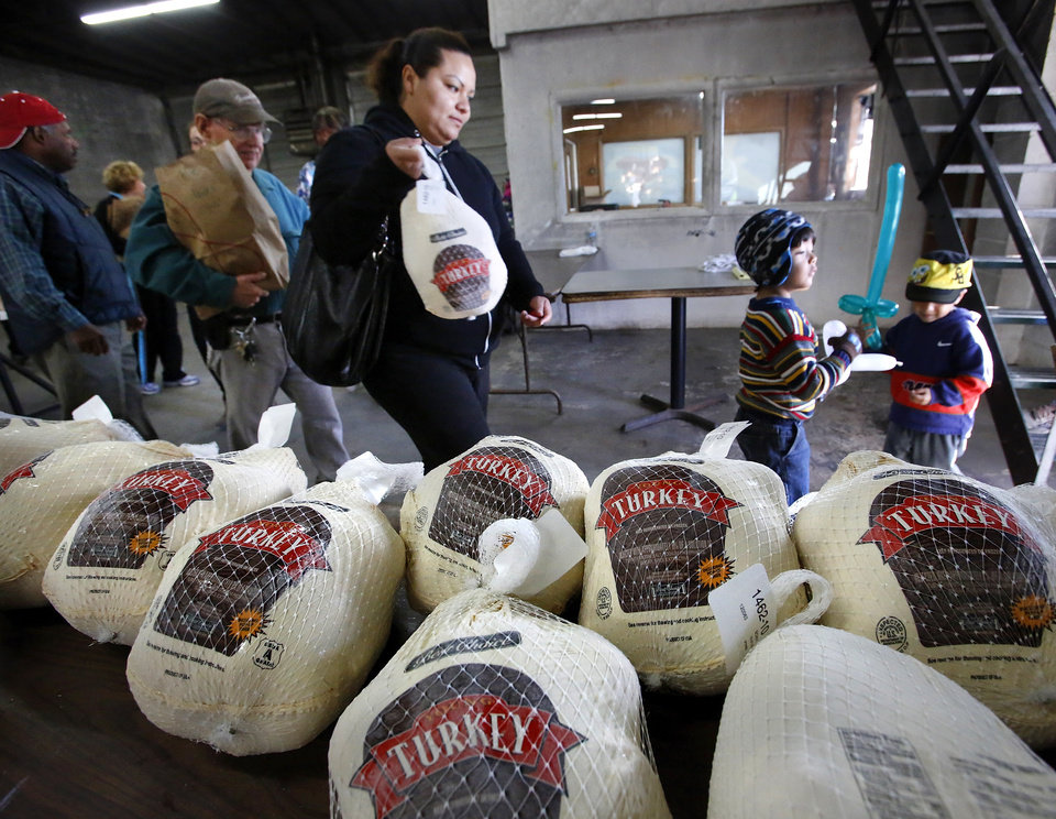 Photo - A woman and two children leave after picking up a turkey and food basket. Jesus House distributed turkeys and grocery items Tuesday morning,  Nov. 19, 2012. Officials said they had 400 turkeys and food baskets to distribute and people were standing in line when their doors opened at 8 a.m. In less than two yours, all turkeys had been claimed. They will pass out 400 more turkeys and food baskets on Wednesday.  Photo by Jim Beckel, The Oklahoman