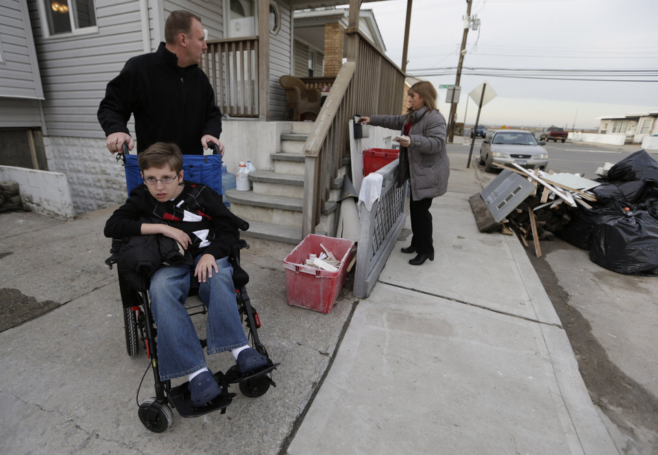 Chris Troy and his wheelchair-bound son Connor, 12, who suffers from a life-threatening neuromuscular disease, waits for wife Kerry Ann to get the mail in Long Beach, N.Y., Wednesday, Dec. 12, 2012, after visiting their home, which is under renovation after it was seriously damaged by Superstorm Sandy. Due to the kindness of strangers, the Troy\'s are staying in a nearby house in Point Lookout, N.Y. All the renovations to the home are being paid for by businessman Donald Denihan, who has ordered his workers to have the Long Beach house ready by Christmas. (AP Photo/Kathy Willens)