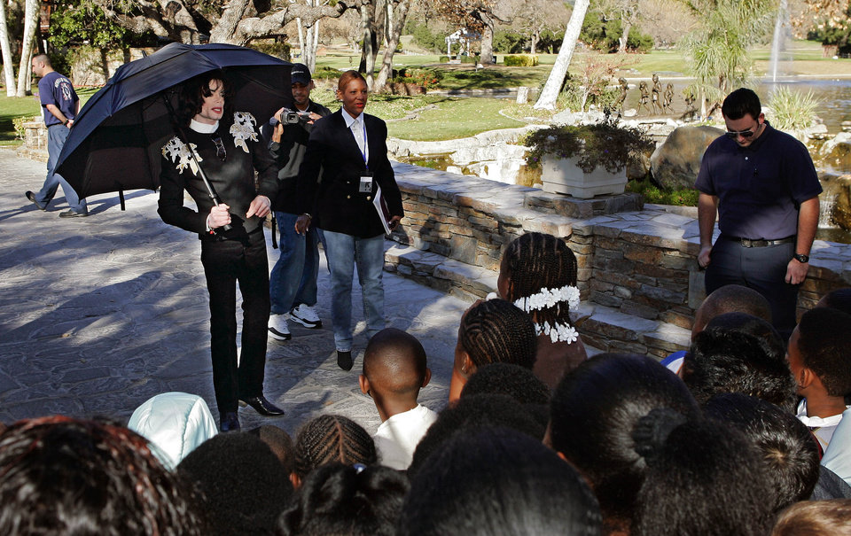 Photo - FILE - In this Dec. 17, 2004 file photo, pop star Michael Jackson greets several hundred children that were invited guests at his Neverland Ranch home, in Santa Ynez, Calif. In 2014, Jackson's playtime palace sits empty now. The backyard circus and laughter of children are long gone, but the house and its fanciful memories live on. (AP Photo/Mark J. Terrill, file)